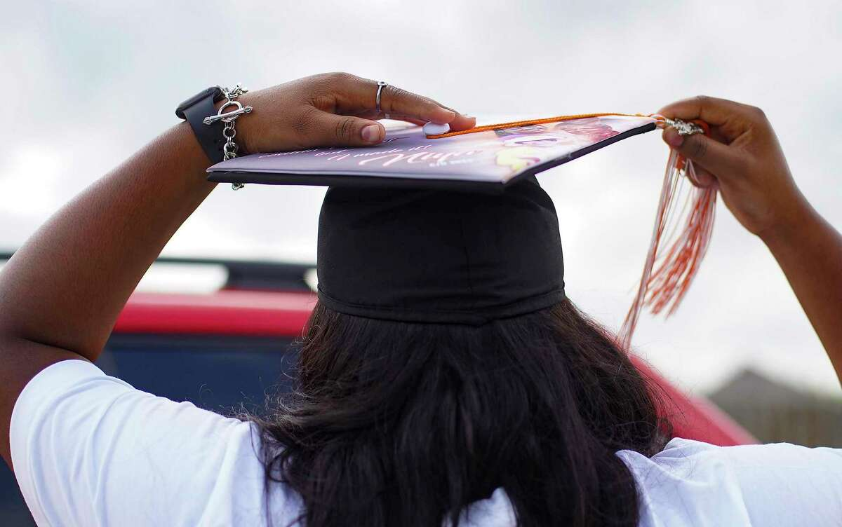 Anaiya Jackson, a senior at Scarborough High School, wears her graduation gown and holds her hat she dedicated to her grandmother who passed away in January in front of her Houston home on Tuesday, May 12, 2020.