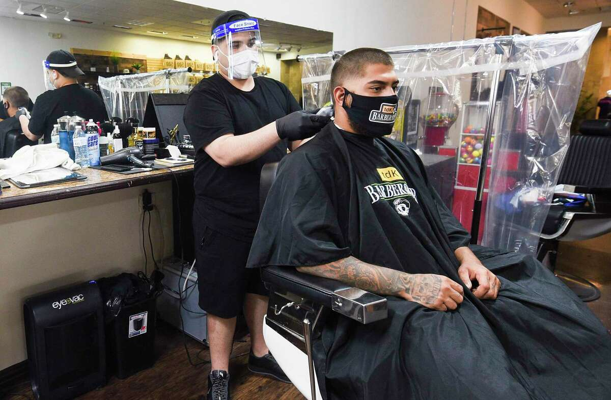 TDK Barber Bori tends to his customer Johnny on Wednesday, May 27 at Mall Del Norte as the barbershop adjusts to the COVID-19 pandemic by separating work stations with plastic sheets.