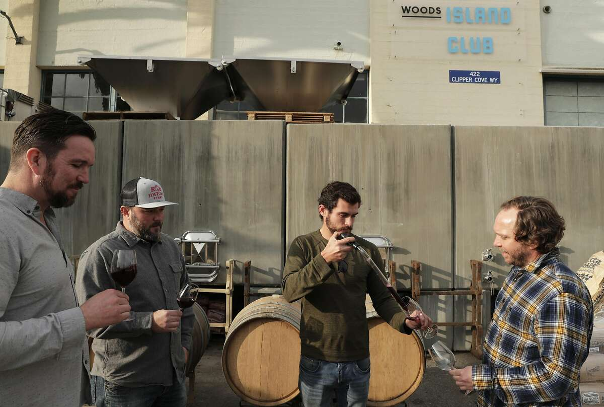 The crew at Wood's Island Club, l-r, Jim Woods, founder and CEO, Chris Scanlan, consulting winemaker, Kyle Jeffrey, assistant winemaker, and Kim Sturdavant, head brewer, in front of the concrete wine tanks at Treasure Island in San Francisco, Calif., on Tuesday, December 10, 2019. A new state law in California, takes effect Jan 1, that will allow wineries, breweries and distilleries to have overlapping licenses. Woods Beer Co. is now also making wine at its Treasure Island facility.