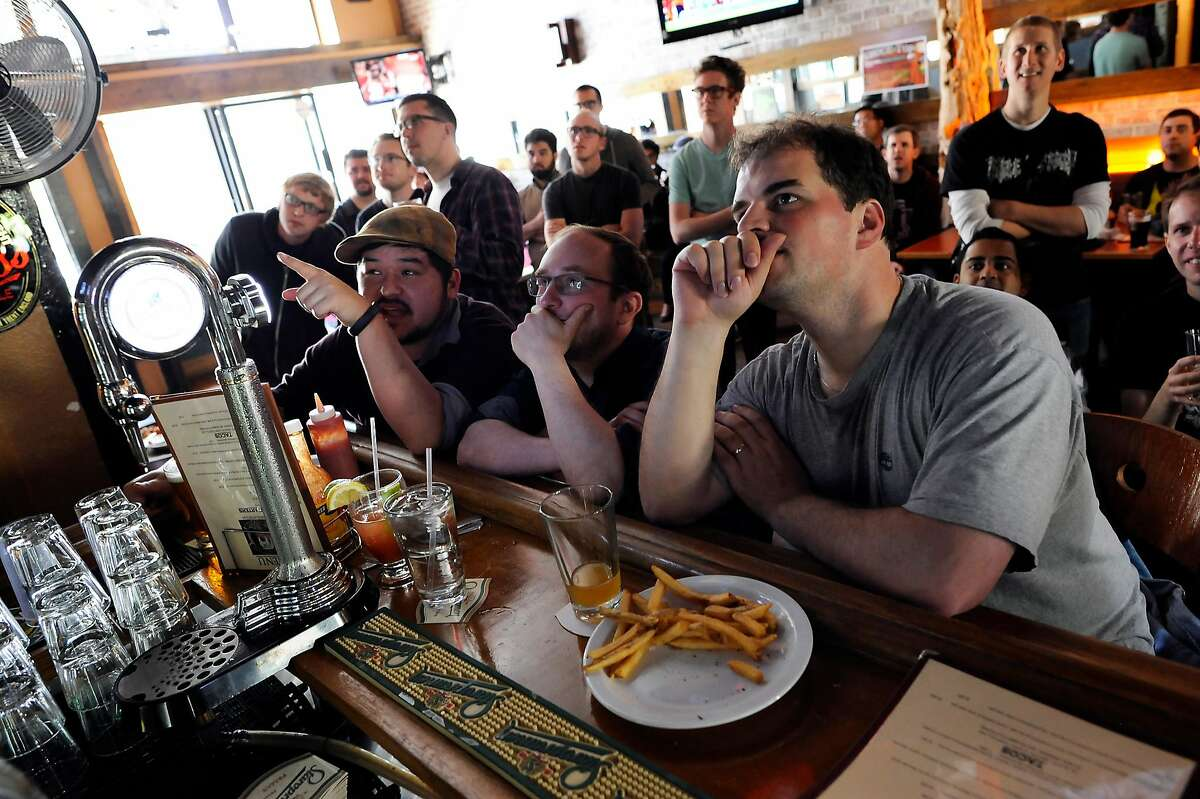 """(L-R)Jake Mix, Aaron Azlant, and Dan Potter discuss tactics being used during the competition as they and others gather around the bar to watch. """"Barcraft"""", a Starcraft video game competition viewing, was held at Mad Dog in the Fog Pub in San Francisco, CA Sunday August 26th, 2012."""