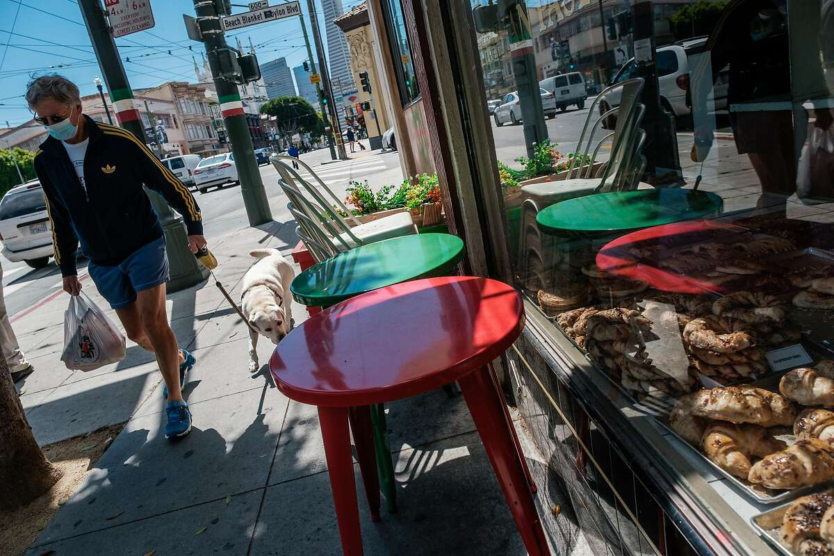 A pedestrian walks past stacked curbside tables and chairs in North beach in San Francisco on Thursday, May 28, 2020.