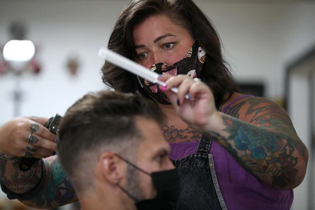 Hair stylist Kayla Van Dyke cuts Todd Maltbie's hair at The Parlor on May 27, 2020 in Napa, California. Hair salons have been given the green light to open in California by Gov. Gavin Newsom with safety measures in place for both customers and workers. It is up to each individual county to decide if they will allow hair salons to reopen under the new guidelines. San Benito, Napa and Solano are among a handful of counties that will see hair salons and barbershops reopening.