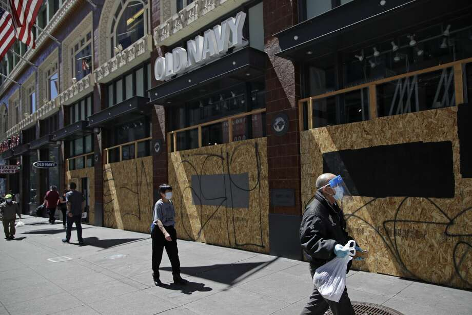 Masked people walk past a boarded up Old Navy clothing store on Wednesday, May 27, 2020, in San Francisco. While much of California moves swiftly to reopen things like hair salons under Gov. Gavin Newsom's guidance, the San Francisco Bay Area is continuing to keep the brakes on. Some health officials are questioning whether the state is taking enough time to assess the effects of reopening things like stores before jumping ahead to broader re-openings, risking a surge in infections. Photo: Ben Margot/Associated Press / Copyright 2020 The Associated Press. All rights reserved.