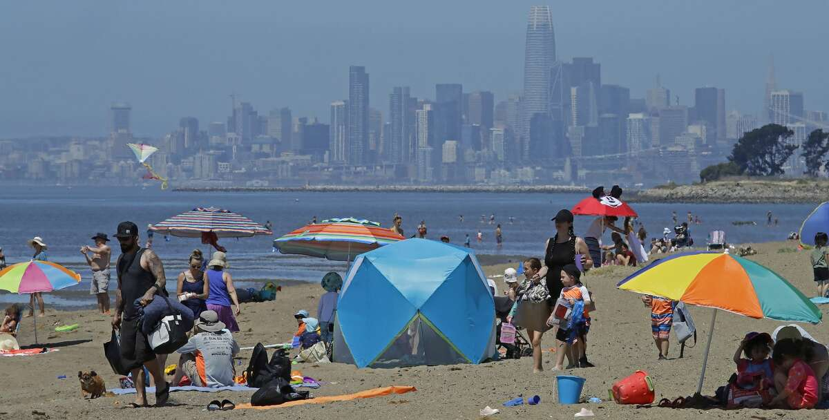 People congregate on Robert W. Crown Memorial State Beach with the San Francisco skyline as a backdrop, Tuesday, May 26, 2020, in Alameda, Calif. The U.S. National Weather Service has issued a heat advisory for the Bay Area through Thursday, May 28, 2020.