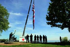Branford firefighters pay respects to an American flag raised as part of the Thank You Tour, which stopped at Connecticut Hospice in Branford Wednesday. The tour aims to serve as respite amid the coronavirus pandemic.