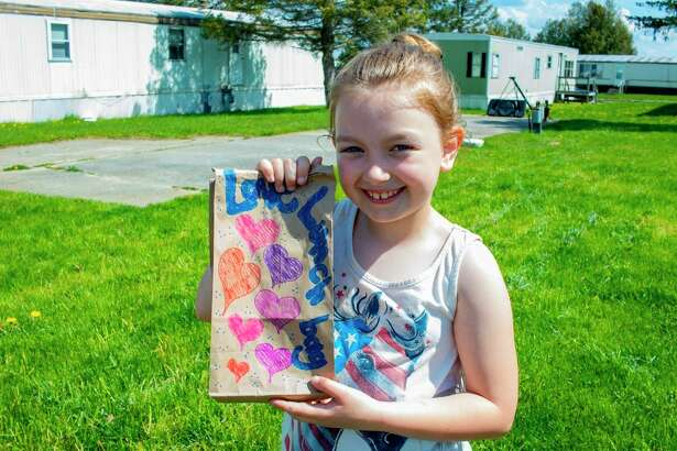 A student shows off her packed lunch during pickup for the current meal program. Angels of Action's new program is set to take place June 8. (Courtesy photo)