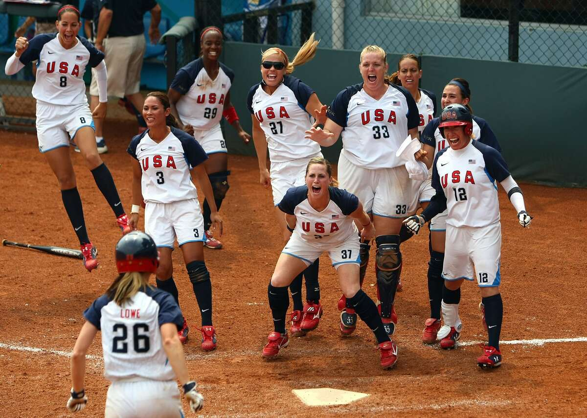 Team USA's Caitlin Lowe is greeted by teammates as she is about to score on a three-run homer by Crystl Bustos in an Aug. 20, 2008 semifinal game against Japan during the 2008 Summer Olympics in Beijing, China.