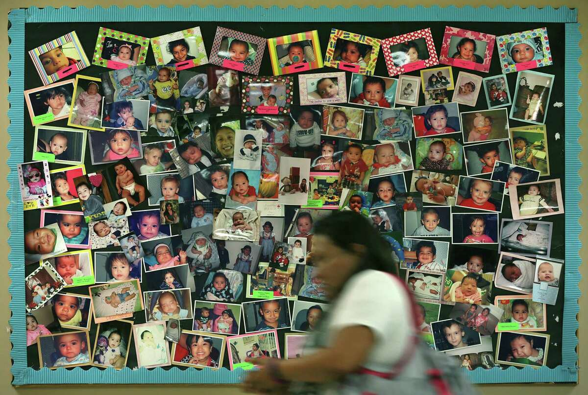 A mother passes a bulletin board with photos of babies born to addicted mothers, at the Center for Health Care Services in 2017. Mothers attend Mommies Class at the center.