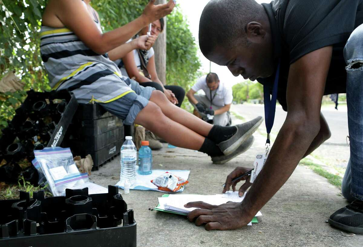 """Sean Baker, an outreach worker with Center for Health Care Services, fills out paperwork in 2017 before performing a blood test on """"Montana"""" checking for HIV, Hep C and syphilis. He made his rounds on North Zarzamora Street handing out personal care bags, water, snacks, and condoms to addicts he finds."""