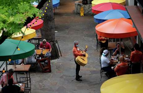 Mariachi musicians, wearing face masks, play for diners at a restaurant that has reopened to 50 percent capacity on the River Walk in San Antonio, Wednesday, May 27, 2020, as the COVID-19 pandemic lessens in the area.