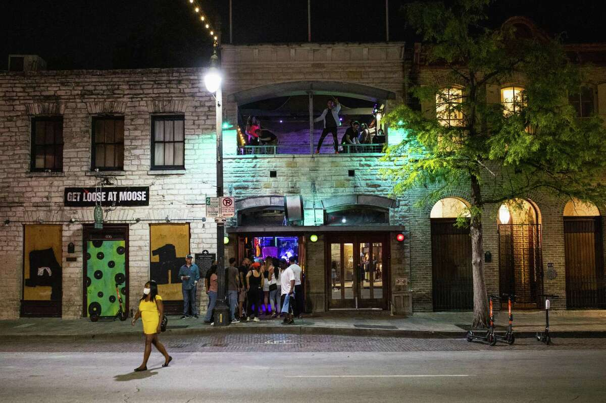 People stand in line to enter a bar on Sixth Street at night in downtown Austin, Texas, U.S., on Saturday, May 23, 2020. Texas bars, bowling alleys and other businesses were able to reopen for the start of Memorial Day weekend as part of Governor Greg Abbott's efforts to revive the state's shattered economy.