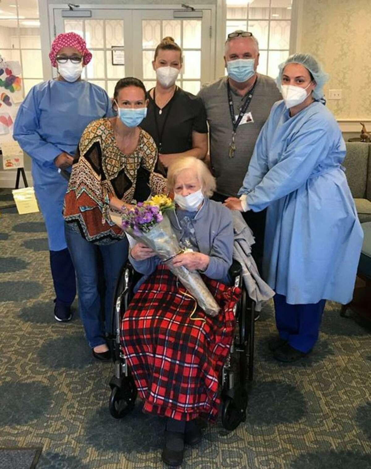 Pauline Romano of East Haven, 101, who survived COVID-19 more than a century after surviving the Spanish Flu pandemic, surrounded by staff at East Haven's Whispering Pines Rehabilitation & Nursing Center, who celebrated her birthday with her May 9 before she was left the facility to go back to her home.