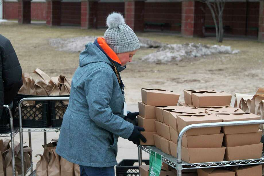 On a cold mid March morning Manistee Area Public Schools Food Service director Keri Carlson prepares to hand out more free breakfast and lunches for the area children under a Michigan Department of Education feeding program. (Ken Grabowski/News Advocate)