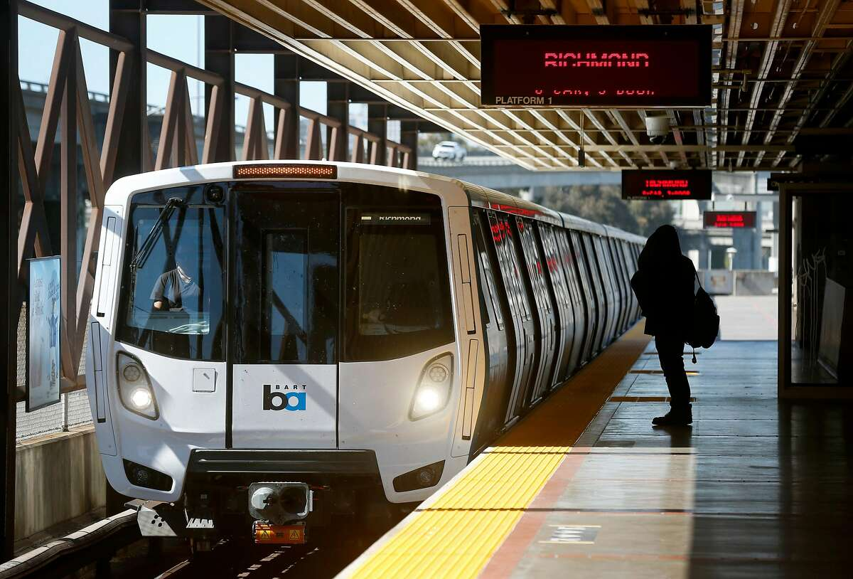 A commuter waits to board a Richmond train arriving at the MacArthur BART station in Oakland. The agency may consider additional cuts as ridership and revenue continue to plummet during the coronavirus pandemic.