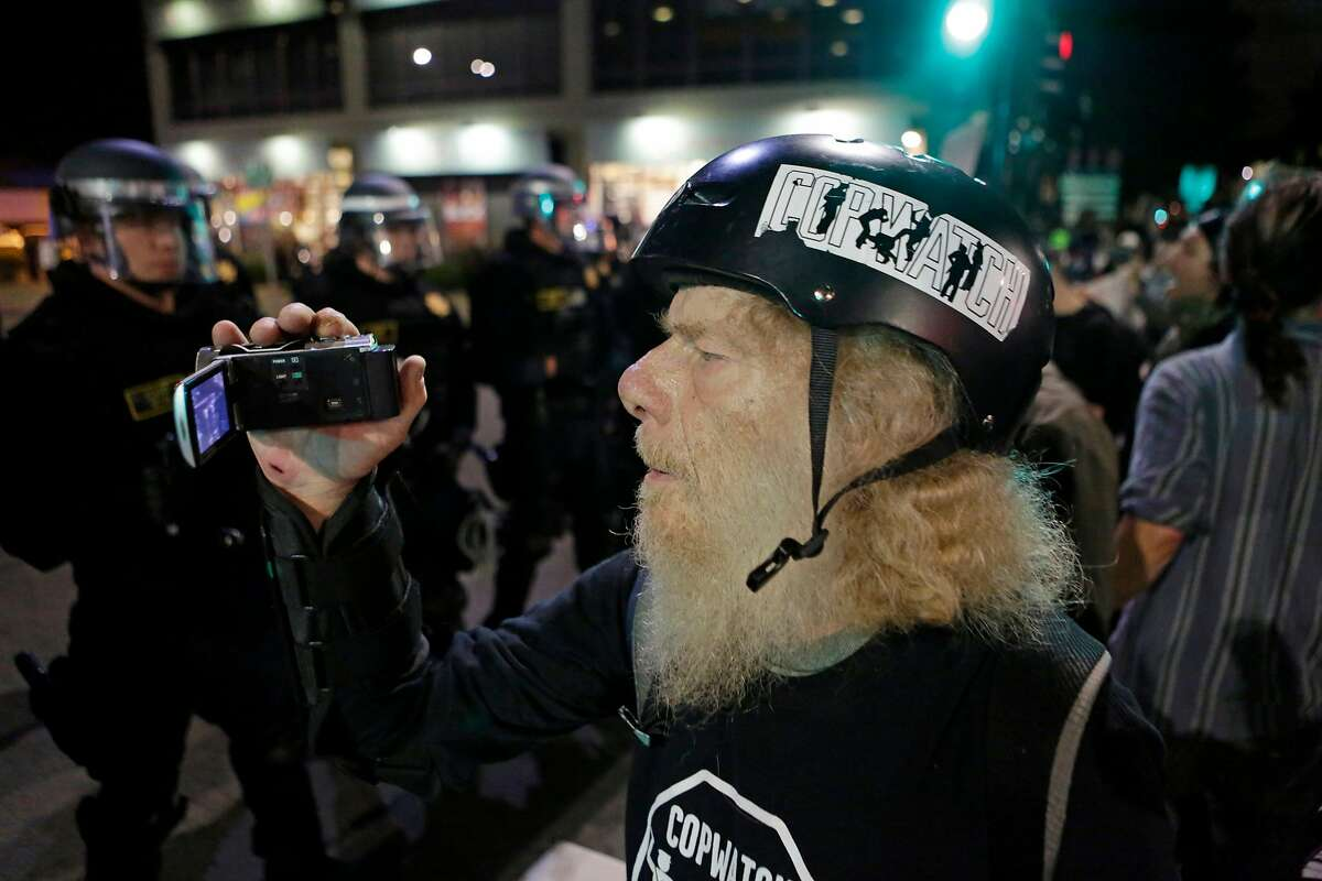 A protester films California Highway Patrol officers on University Avenue in Berkeley on Monday, December 8, 2014. The protest was past of an ongoing response to police violence against unarmed black men, including the shooting of Michael Brown in Ferguson, MO, and the choking of Eric Garner in New York.