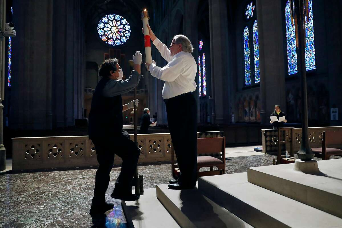 Charles Shipley (right) and John Horton place a candle before virtual Easter Sunday service at Grace Cathedral in San Francisco, Calif., on Sunday, April 12, 2020.