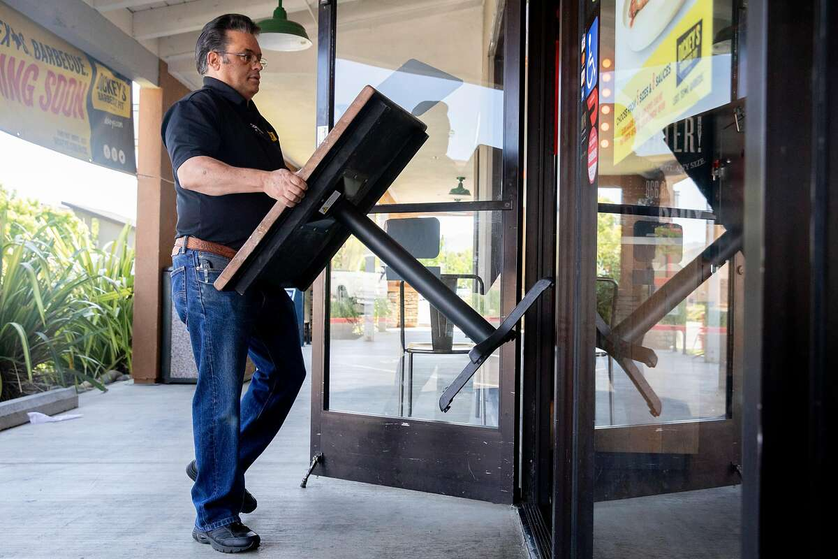 Dickey's Barbecue Pit owner Rene Bassett brings in tables and chairs from outside of his restaurant in Napa, Calif. Tuesday, May 5, 2020. Bassett planned to open his restaurant to in-house and outdoor seating Tuesday but his plans were put on pause by the local health inspector.