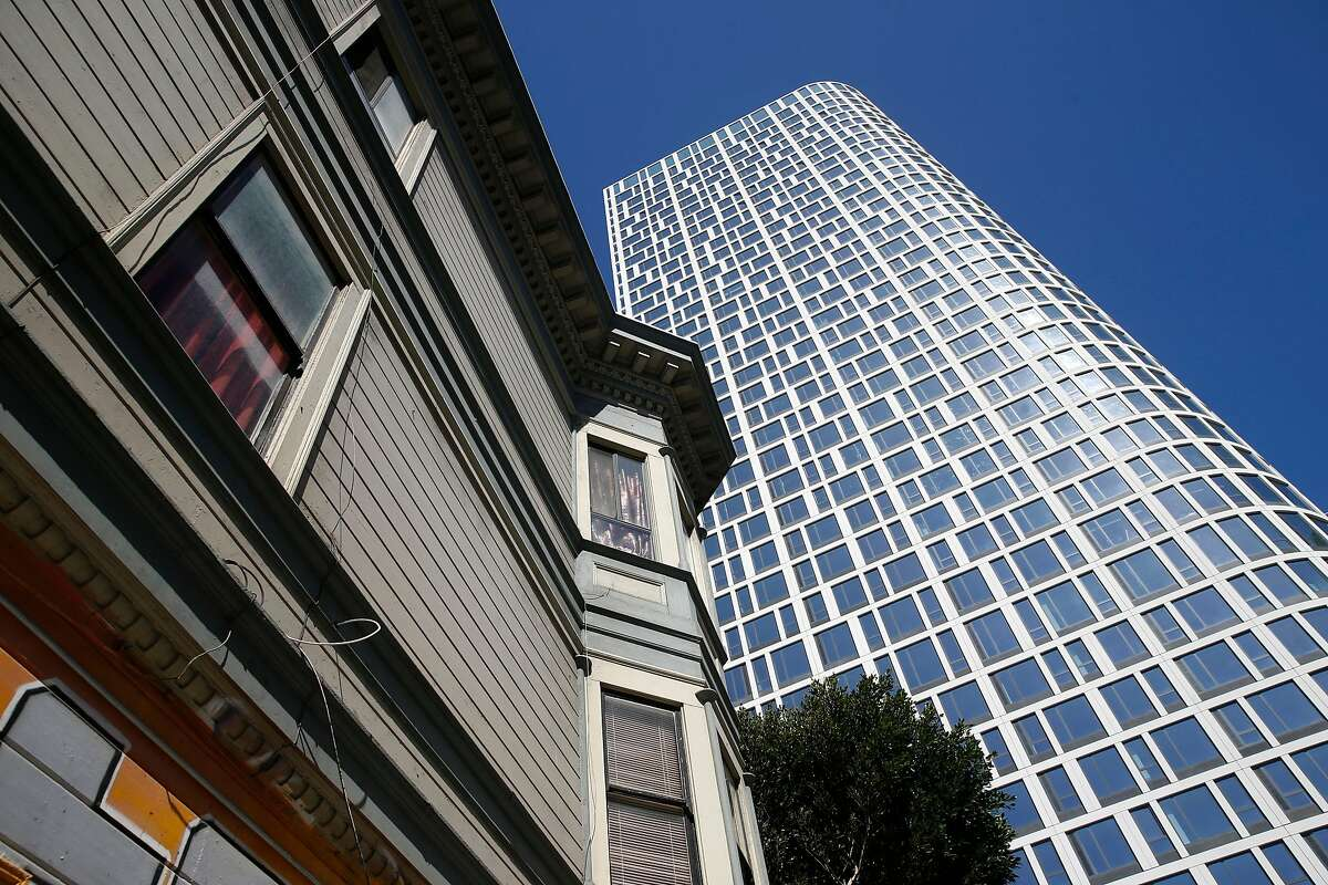 Lowrise apartment buildings on Lafayette Street are dwarfed by a 40-story residential tower nearing completion at 1550 Mission Street in San Francisco, Calif. on Wednesday, May 27, 2020.