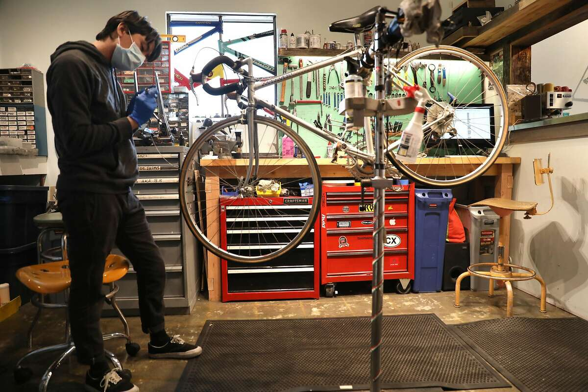 Bike mechanic Eddy Bachworks on a wheel of a vintage Peugeot at Swell Bicycles on Thursday, May 28, 2020, in San Francisco, Calif.
