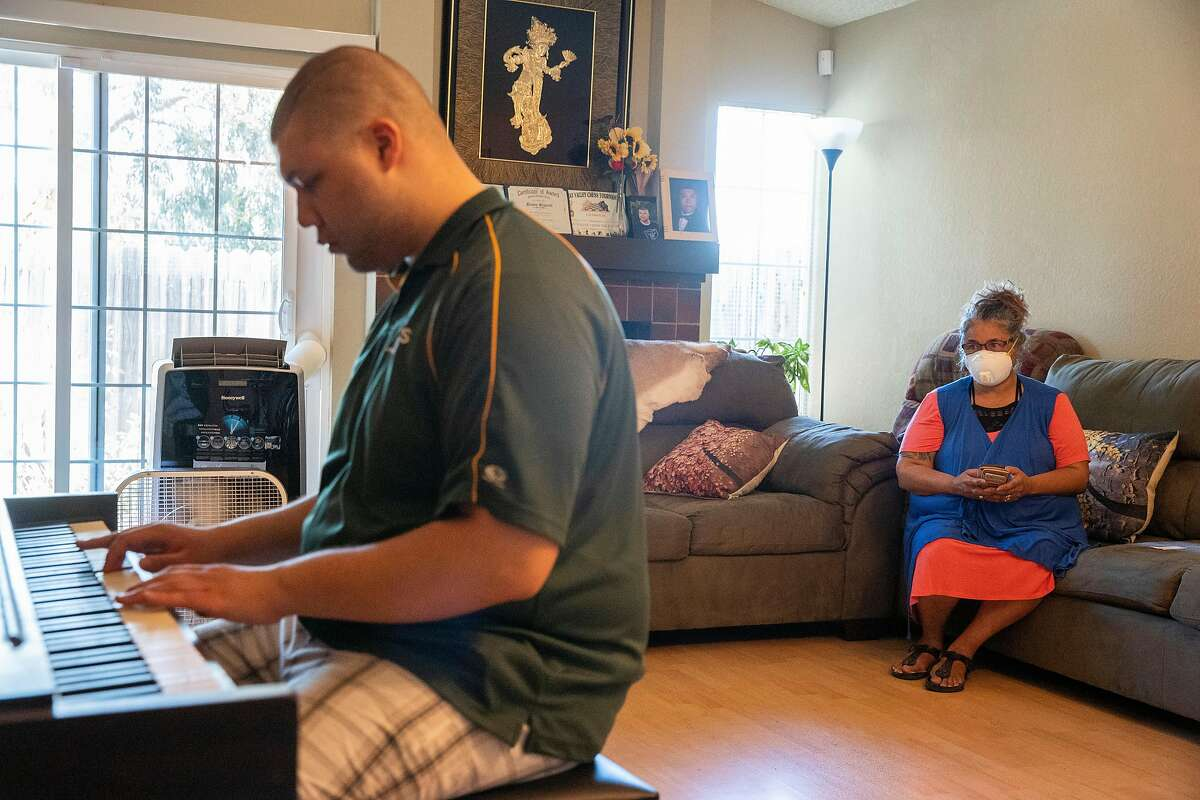 From left: Brennon Bluntach plays the piano as his mother Bellinda watches at home on Tuesday, May 26, 2020, in Hercules, Calif. Brennon, a 22-year-old who is diagnosed with autism, takes online classes to keep a routine, amid the shelter-in-place orders due to the coronavirus pandemic. The classes involve socializing, stretching and dancing, among other activities. Brennon also plays the piano for leisure. Brennon said he loves Beethoven and Mozzart songs.