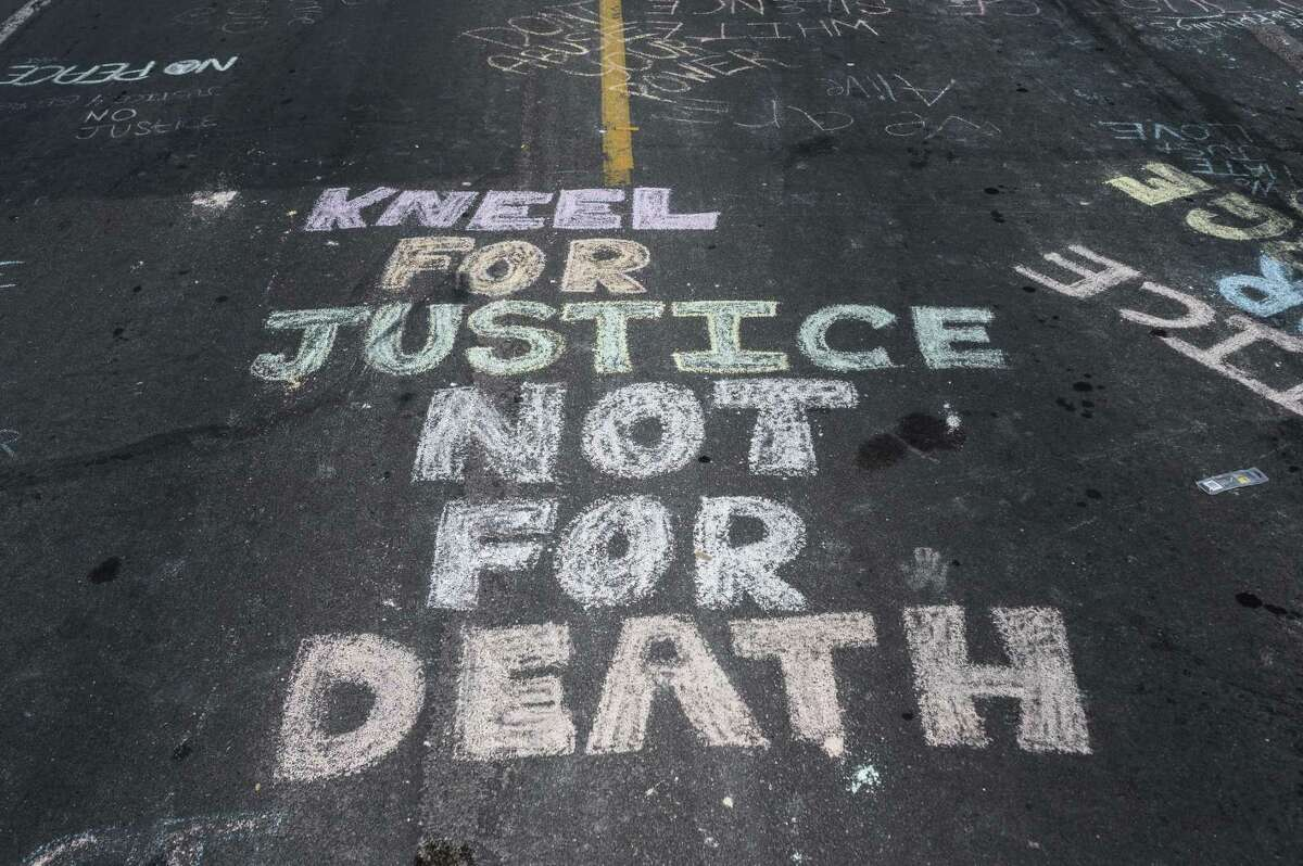 """MINNEAPOLIS, MN - MAY 28: """"Kneel for Justice not for Death"""" is written on the road outside the Cup Foods, where George Floyd was killed in police custody, on May 28, 2020 in Minneapolis, Minnesota. People have gathered at the site since Floyd was killed earlier this week. (Photo by Stephen Maturen/Getty Images)"""