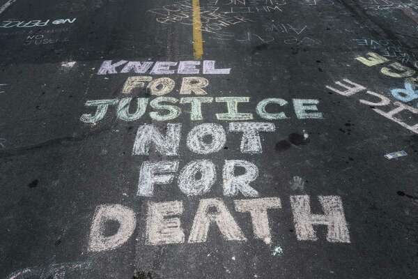 "MINNEAPOLIS, MN - MAY 28: ""Kneel for Justice not for Death"" is written on the road outside the Cup Foods, where George Floyd was killed in police custody, on May 28, 2020 in Minneapolis, Minnesota. People have gathered at the site since Floyd was killed earlier this week. (Photo by Stephen Maturen/Getty Images)"