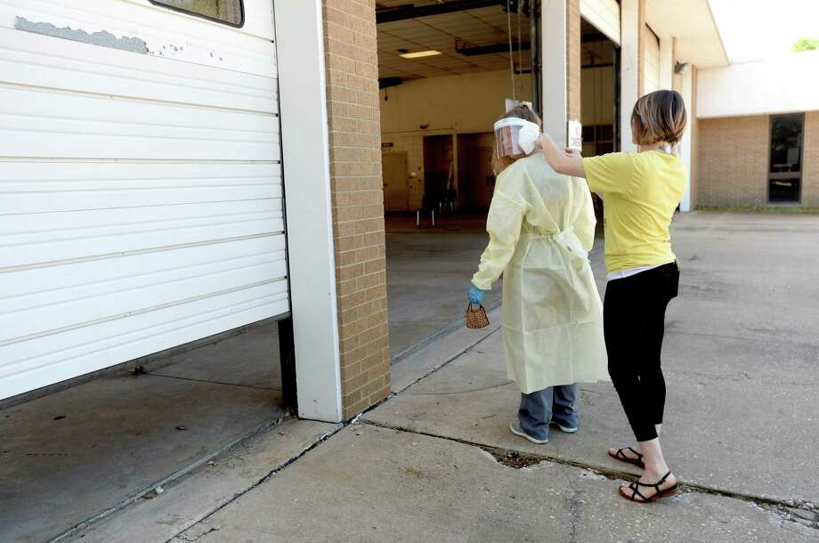 Riceland's Brittany Givens helps tie up a gown for a healthcare worker manning a testing station at the former Beaumont Fire Station #1 Tuesday. Testing will continue at the site through Thursday. Appointments must be made, although there are no symptom requirements to obtain the test. Riceland will set up again in two weeks for another round of testing. Mayor Becky Ames encourages citizens to get tested and continue to practice safety measures, including wearing masks and observing social distancing. She also stronlgly enncourages those who have recovered to donate plasma, which contains antibodies that have proven useful in treating those fighting the virus.