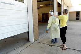 Riceland's Brittany Givens helps tie up a gown for a healthcare worker manning a testing station at the former Beaumont Fire Station #1 Tuesday. Testing will continue at the site through Thursday. Appointments must be made, although there are no symptom requirements to obtain the test. Riceland will set up again in two weeks for another round of testing. Mayor Becky Ames encourages citizens to get tested and continue to practice safety measures, including wearing masks and observing social distancing. She also stronlgly enncourages those who have recovered to donate plasma, which contains antibodies that have proven useful in treating those fighting the virus. Photo taken Tuesday, May 19, 2020 Kim Brent/The Enterprise