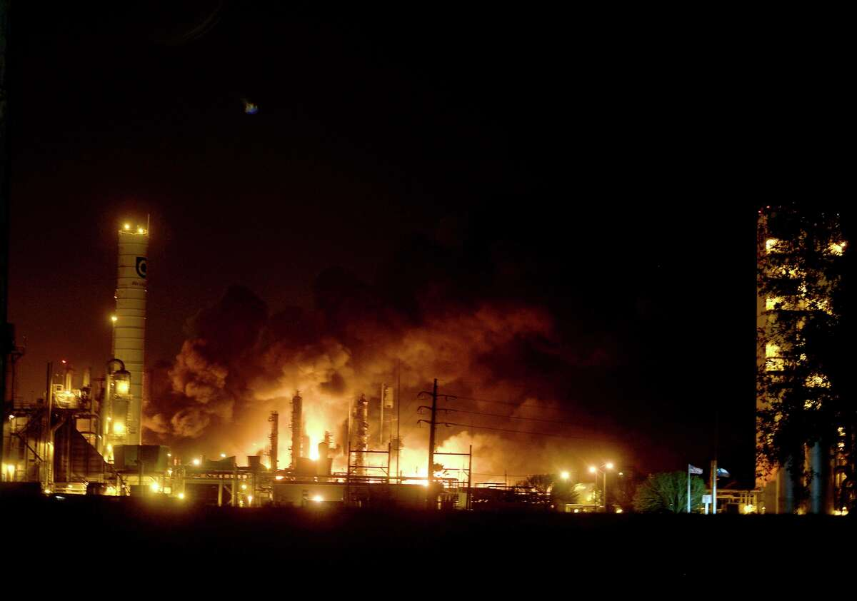 FILE - In this Wednesday, Nov. 27, 2019, file photo, flames and thick, black smoke light up the pre-dawn sky following and explosion at the TPC plant in Port Neches, Texas. The Occupational Safety and Health Administration said that it cited TPC for three willful violations by not developing and implementing procedures for emergency shutdown and not inspecting and testing process vessel and piping components. TPC faces $514,692 in civil OSHA fines, stemming from the explosion and fires. (Kim Brent/The Beaumont Enterprise via AP)