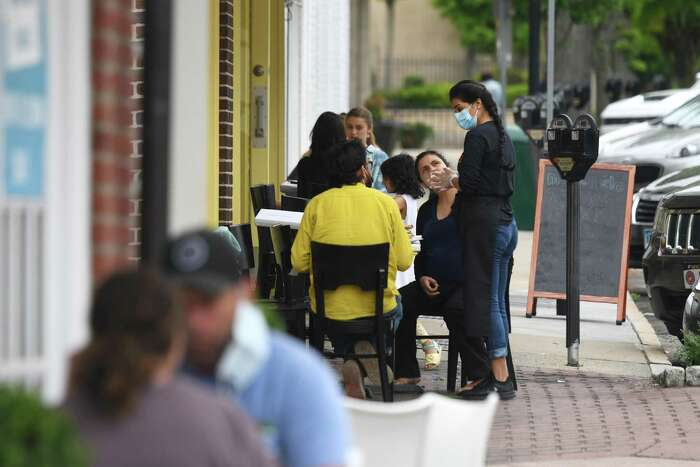 A crowd dines outside at Meli-Melo on Greenwich Avenue in Greenwich, Conn. Thursday, May 28, 2020. The southern end of Greenwich Avenue from Arch Street to Railroad Avenue will be closed off to vehicular traffic to be used as an area for pedestrians and outdoor dining.