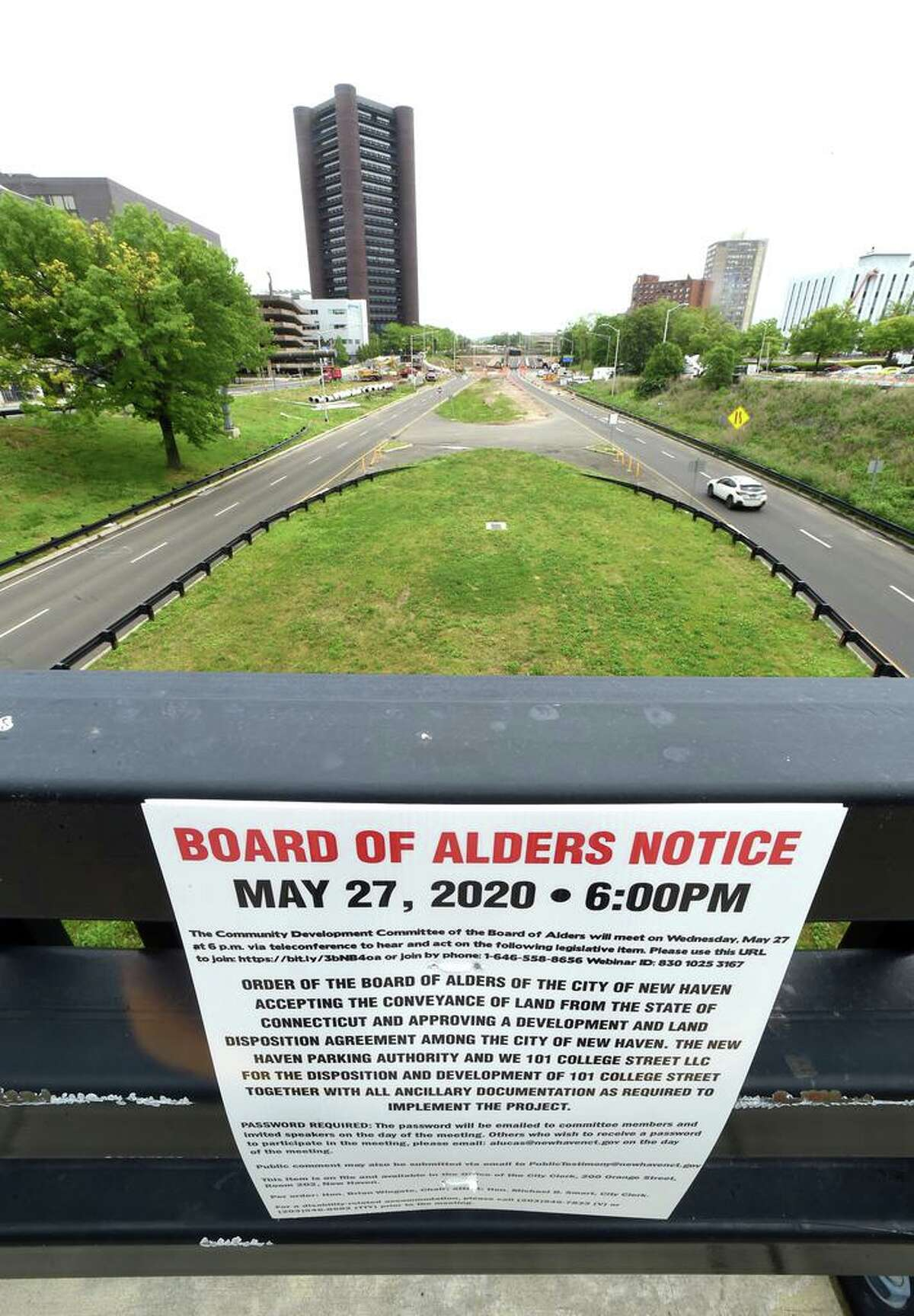 A New Haven Board of Alders notice hangs on a railing at 101 College Street in New Haven on May 28, 2020 detailing a conveyance of land from the state at this location and approval of development and land disposition agreement.