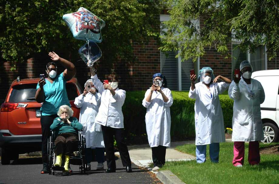 Patients and staff members wave to those driving by Wilton Meadows in the Heroes Parade on Wednesday, May 27. Photo: H John Voorhees III / Hearst Connecticut Media / The News-Times