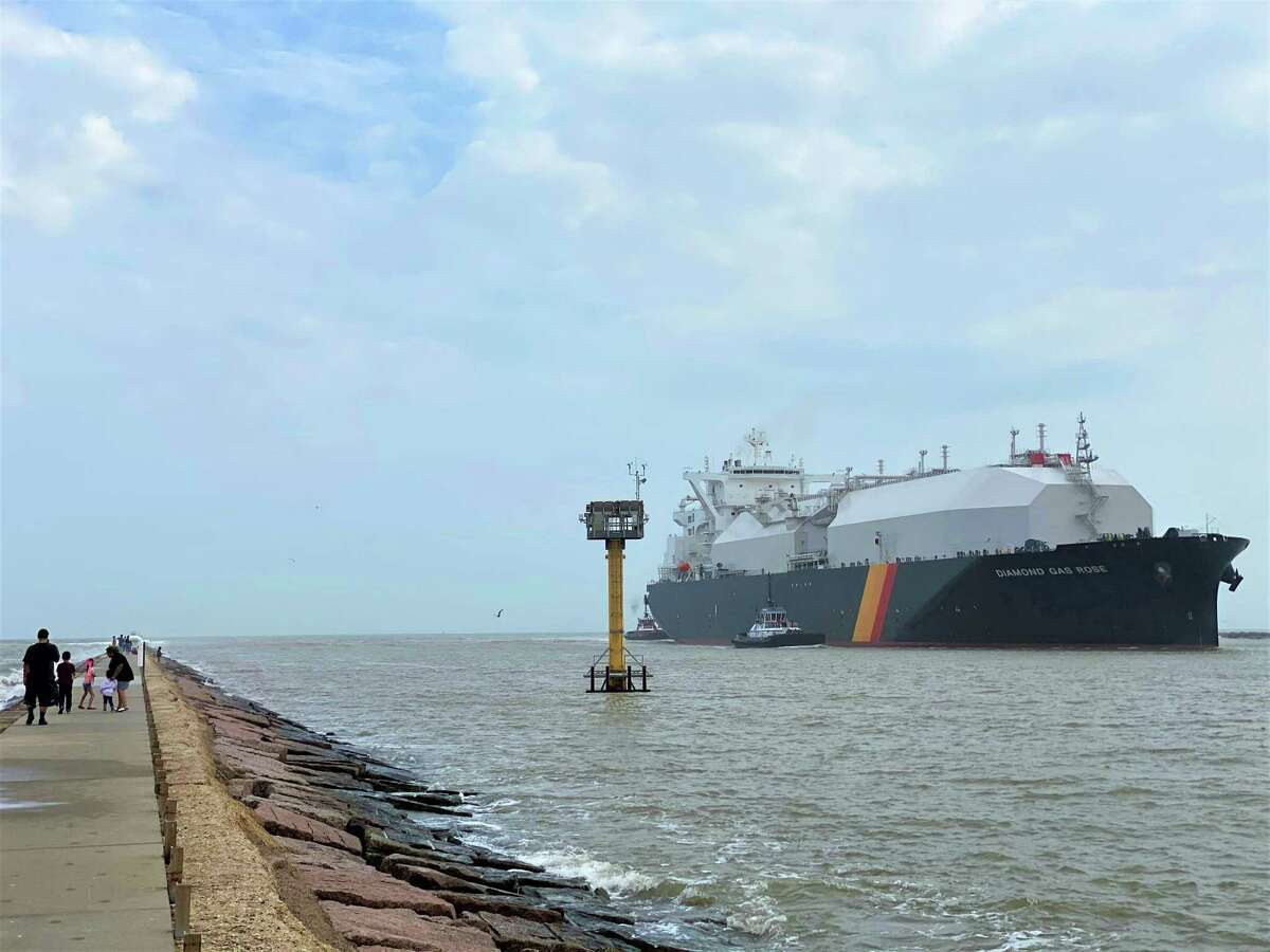 Families and surfers are indifferent as a liquefied natural gas tanker named the Diamond Gas Rose enters the Freeport Ship Channel at Surfside Beach.