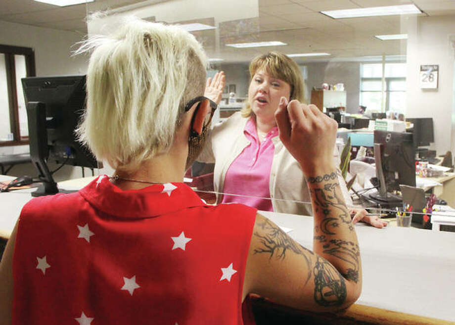 Jennifer Ferguson, of the Madison County Clerk's Office, takes an oath from Casey Fayollat, of Troy, who was getting a marriage license at the Clerk's Office. The Plexiglas shield Ferguson is behind is among a number of ways the county is dealing with the COVID-19 pandemic. Because she is behind the screen, Ferguson does not have to wear a mask.