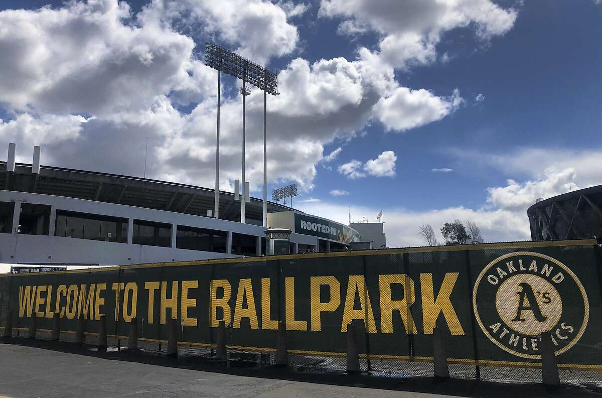 """FILE - This March 25, 2020, file photo shows a banner to welcome to fans at the Oakland-Alameda County Coliseum in Oakland, Calif. The Athletics are placing their scouts and a significant number of other front office employees on furlough, suspending pay for minor leaguers and cutting the salaries of other executives as part of a cost-cutting move in response to the COVID-19 pandemic. A's owner John Fisher announced the moves Tuesday, May 26, 2020, in a rare public statement on what he called a """"tremendously difficult day."""" (AP Photo/Ben Margot, File)"""