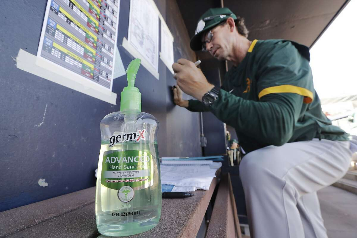 Oakland Athletics minor league manager Scott Steinmann fills-out a line-up in the MLB team's dugout next to a bottle of hand sanitizer before a spring training baseball game against the Seattle Mariners Saturday, March 7, 2020, in Peoria, Ariz. (AP Photo/Elaine Thompson)