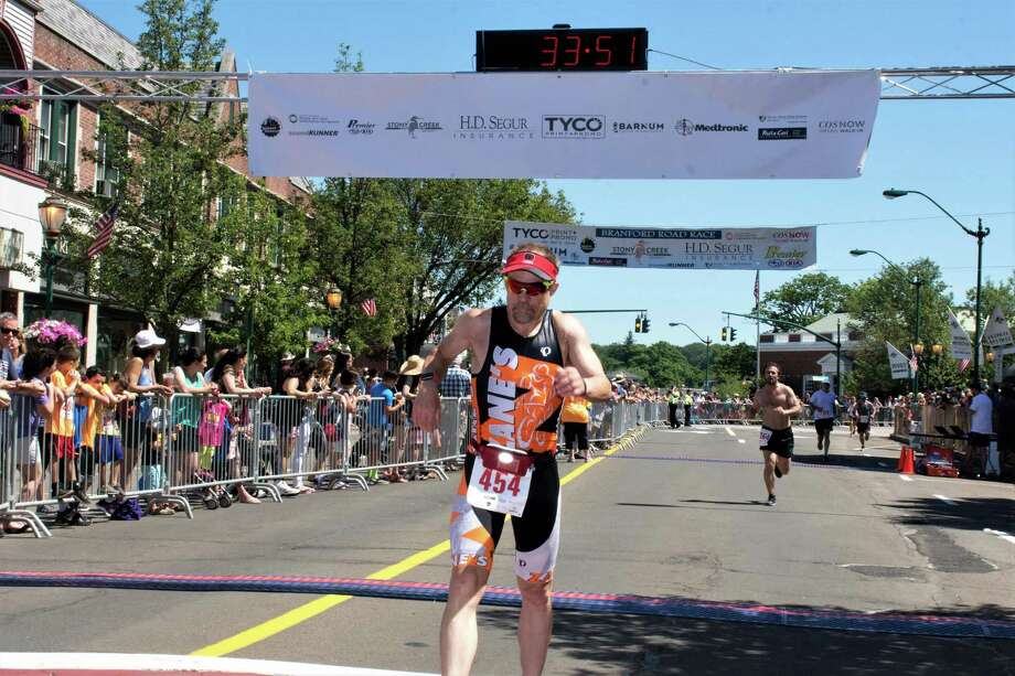 Branford's Alan Mcdougall, pictured here crossing the finish line at the Branford Road Race, is adjusting to competing in virtual road races. The Branford Road Race, held each Father's Day since 1979, will be virtual this year. Photo: Contributed/Bill O'Brien