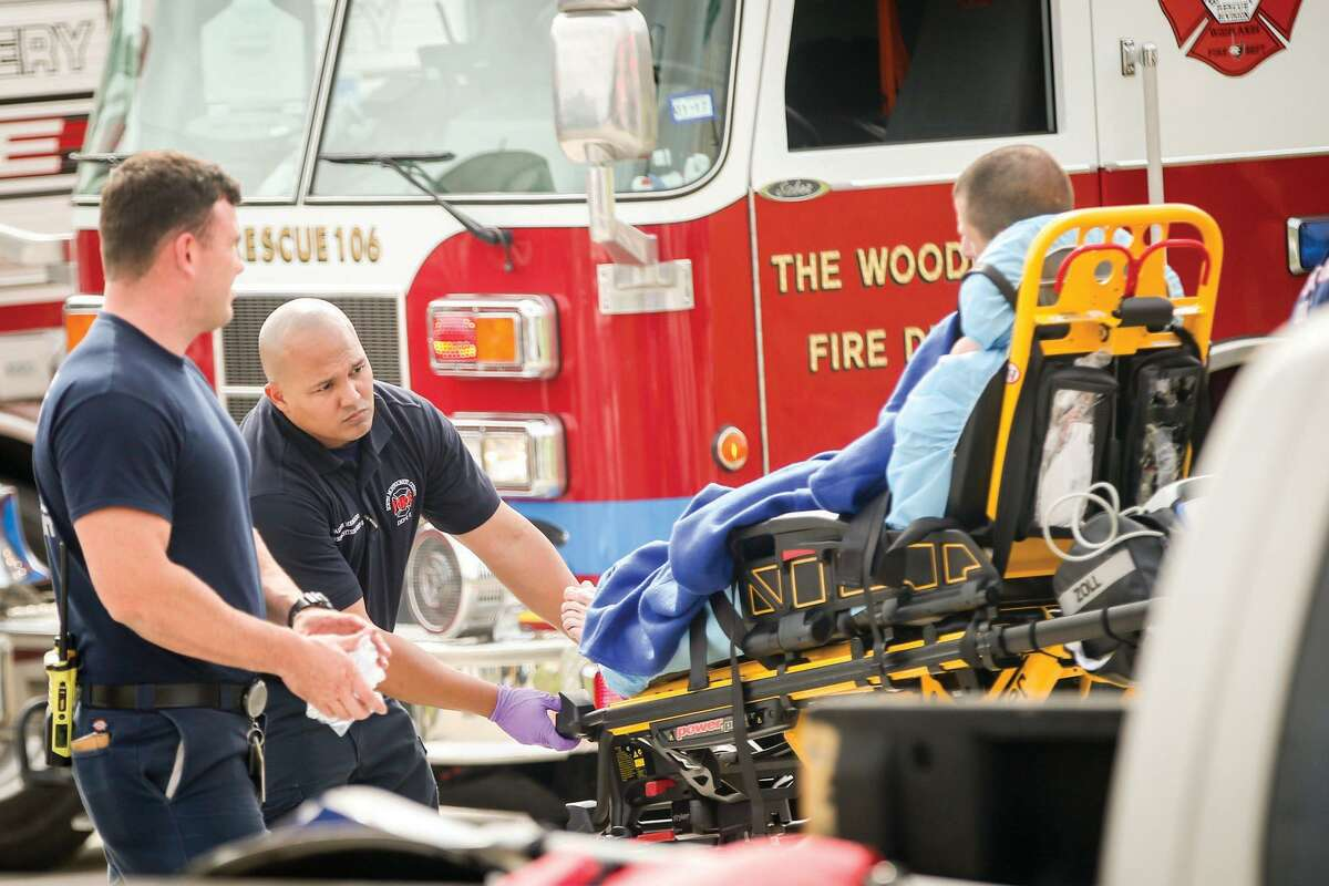 South Montgomery County firefighters load citizens into an ambulance after they were rescued from a flooded creek on Monday, April 18, 2016, in Spring.