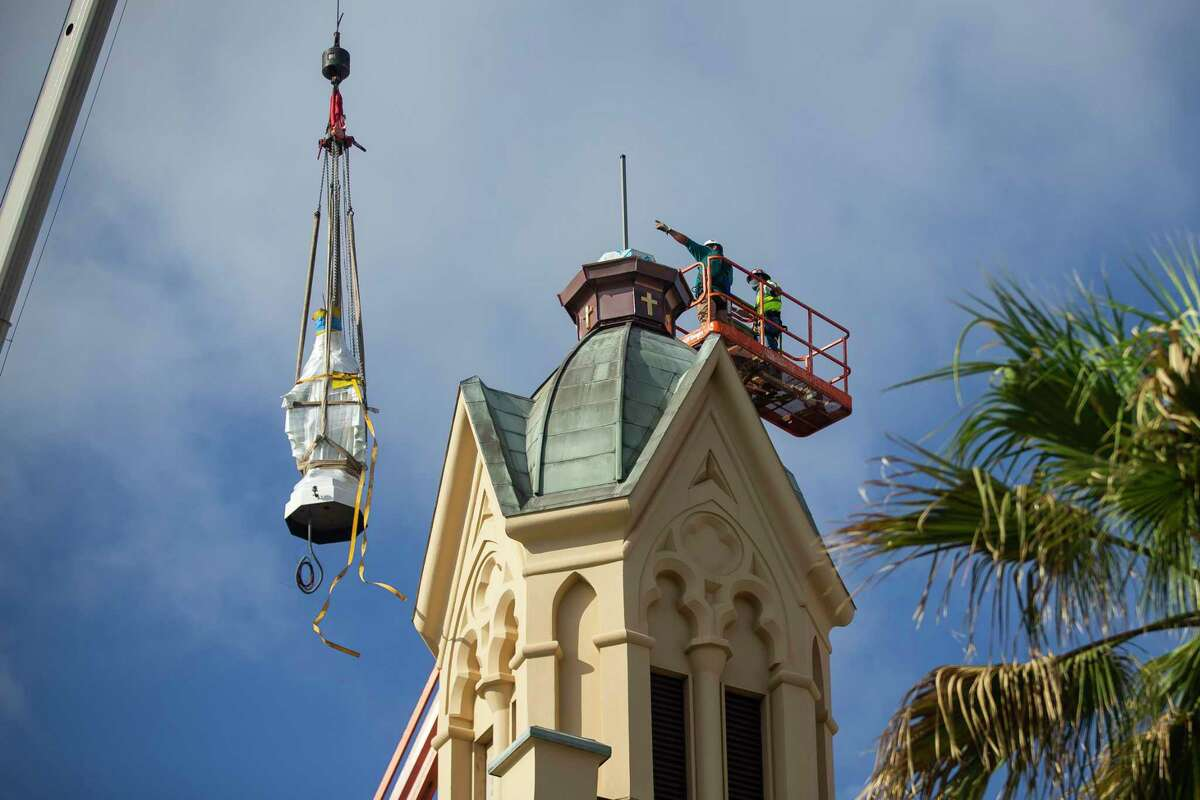 Workers lift up the statue of the Virgin Mary to reinstall it on top of St. Mary's Cathedral Basilica after the statue was refurbished, Thursday, May 28, 2020, in Galveston. The cathedral was completed in 1847 and notably survived the hurricane of 1900. Many people there to witness the statue be placed back on top of the cathedral say that they are used to looking up to the top of the cathedral for the statue of Mary to know everything is OK after a storm.