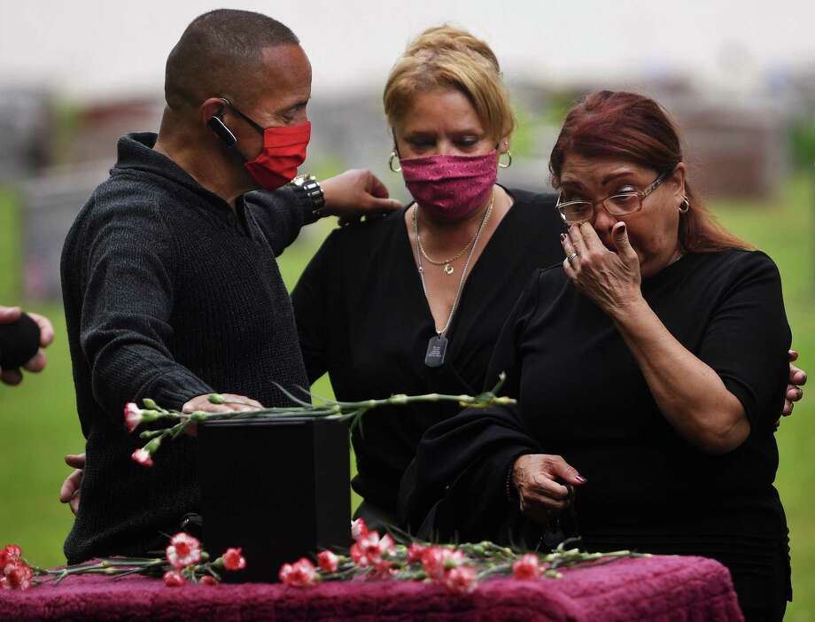 From left, siblings Alberto, Isabel,and Milagros DeLeon, all of Bridgeport, say goodbye to their brother Carlos during his funeral at St. Michael's Cemetary in Stratford on Thursday. Photo: Brian A. Pounds / Hearst Connecticut Media / Connecticut Post