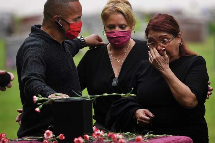 From left, siblings Alberto, Isabel,and Milagros DeLeon, all of Bridgeport, say goodbye to their brother Carlos during his funeral at St. Michael's Cemetary in Stratford on Thursday.
