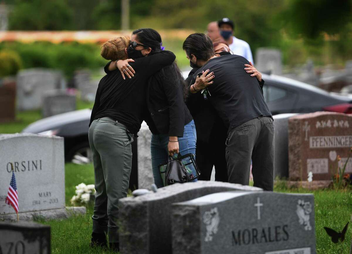 Family members of Carlos DeLeon share hugs as they gather for his graveside funeral service at St. Michael's Cemetary in Stratford, Conn. on Thursday, May 28, 2020.