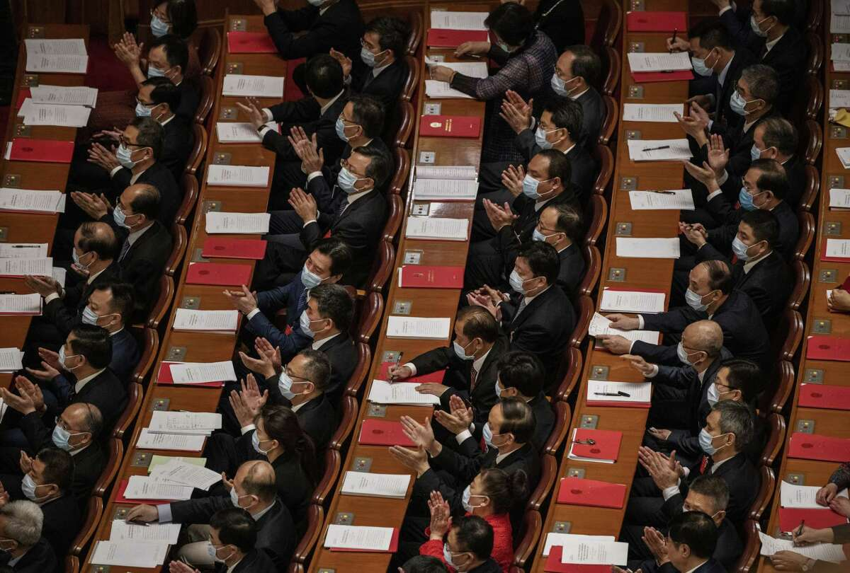 BEIJING, CHINA - MAY 28: Communist Party delegates applaud during the closing session of the National People's Congress, which included a vote on a new draft security bill for Hong Kong, at the Great Hall of the People on May 28, 2020 in Beijing, China. The Chinese government passed the draft by a vote of 2,878 votes to one during the session. The draft law, which has drawn international concern, is set to address issues such as secession, subversion, terrorism, and foreign interference, comes after a year of anti-government protests in the semi-autonomous region. China held its annual parliamentary gathering, known as 'The Two Sessions', at the Great Hall of the People from May 21-28th after being postponed at the height of the coronavirus outbreak in China earlier this year. (Photo by Kevin Frayer/Getty Images)