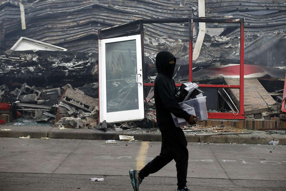 A man carries items past a burned out Auto Zone store near the Minneapolis Police Third Precinct Thursday, May 28, 2020, after a night of rioting and looting as protests continue over the death of George Floyd, who was seen on video gasping for breath during an arrest in which an officer kneeled on his neck. (AP Photo/Jim Mone)