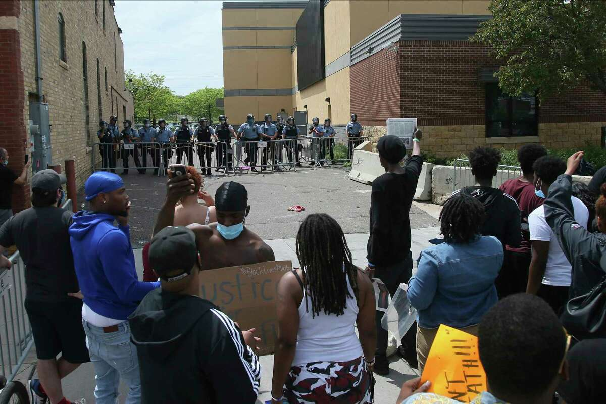 Minneapolis police stand guard against protesters at the Third Precinct Wednesday, May 27, 2020 as people protest the arrest and death of George Floyd who died in police custody Monday night in Minneapolis after video shared online by a bystander showed a white officer kneeling on his neck during his arrest as he pleaded that he couldn't breathe. (AP Photo/Jim Mone)