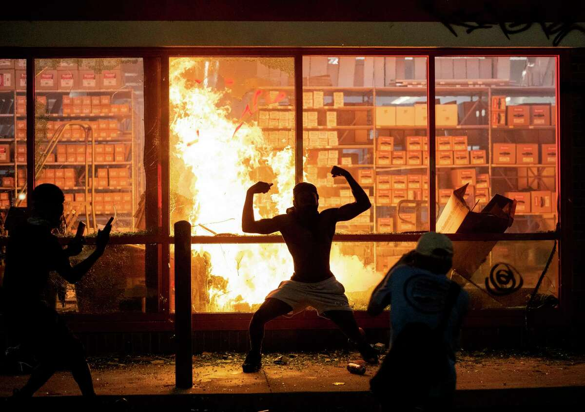 A man poses for photos in front of a fire at an AutoZone store, while protesters hold a rally for George Floyd in Minneapolis on Wednesday, May 27, 2020. Violent protests over the death of the black man in police custody broke out in Minneapolis for a second straight night Wednesday, with protesters in a standoff with officers outside a police precinct and looting of nearby stores. (Carlos Gonzalez/Star Tribune via AP)