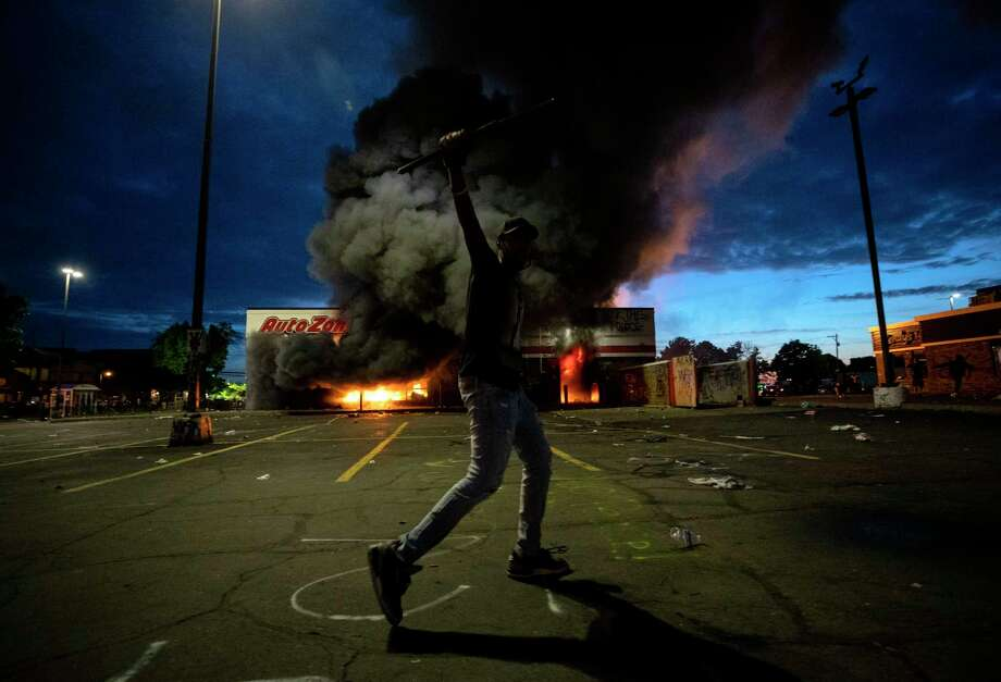 A man poses for a photo in the parking lot of an AutoZone store in flames, while protesters hold a rally for George Floyd in Minneapolis on Wednesday, May 27, 2020. Violent protests over the death of the black man in police custody broke out in Minneapolis for a second straight night Wednesday, with protesters in a standoff with officers outside a police precinct and looting of nearby stores. (Carlos Gonzalez/Star Tribune via AP) Photo: Carlos Gonzalez / © 2020 Carlos Gonzalez /Star Tribune