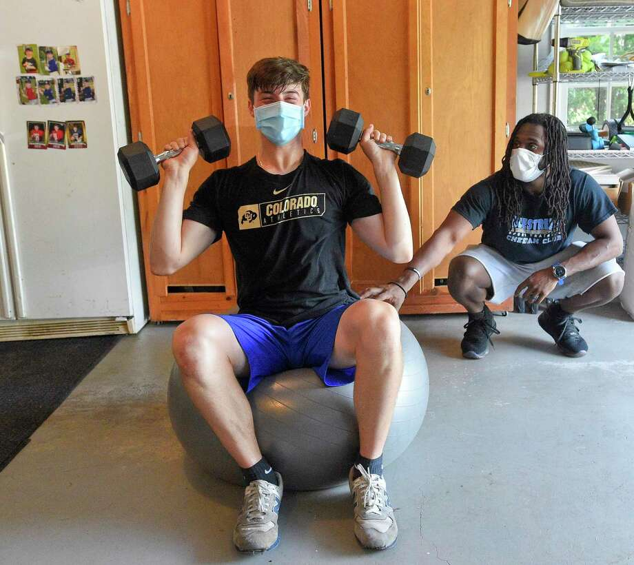 Ali Knott, at right, works with student athlete Ben Pennella, a Junior at Westhill High School at Pennella's workout studio set up in his families garage in Stamford, Connecticut on May 27, 2020. Knott, who left his position as the Strength and Conditioning coach with Westhill in the fall of 2019, to devote more time to his current employer BlueStreak Sports Training of Stamford, works with other student athletes in a virtual workout format, but often visits athletes for a one to one workout in a socially acceptable distancing session. Today's session consisted of working the upper and lower parts of the body, using weights, resistant bands, and weight ropes. Each student keeps a log of their workouts, that can be reviewed and modified to meet each individual strengths. Photo: Matthew Brown / Hearst Connecticut Media / Stamford Advocate