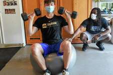 Ali Knott, at right, works with student athlete Ben Pennella, a Junior at Westhill High School at Pennella's workout studio set up in his families garage in Stamford, Connecticut on May 27, 2020. Knott, who left his position as the Strength and Conditioning coach with Westhill in the fall of 2019, to devote more time to his current employer BlueStreak Sports Training of Stamford, works with other student athletes in a virtual workout format, but often visits athletes for a one to one workout in a socially acceptable distancing session. Today's session consisted of working the upper and lower parts of the body, using weights, resistant bands, and weight ropes. Each student keeps a log of their workouts, that can be reviewed and modified to meet each individual strengths.