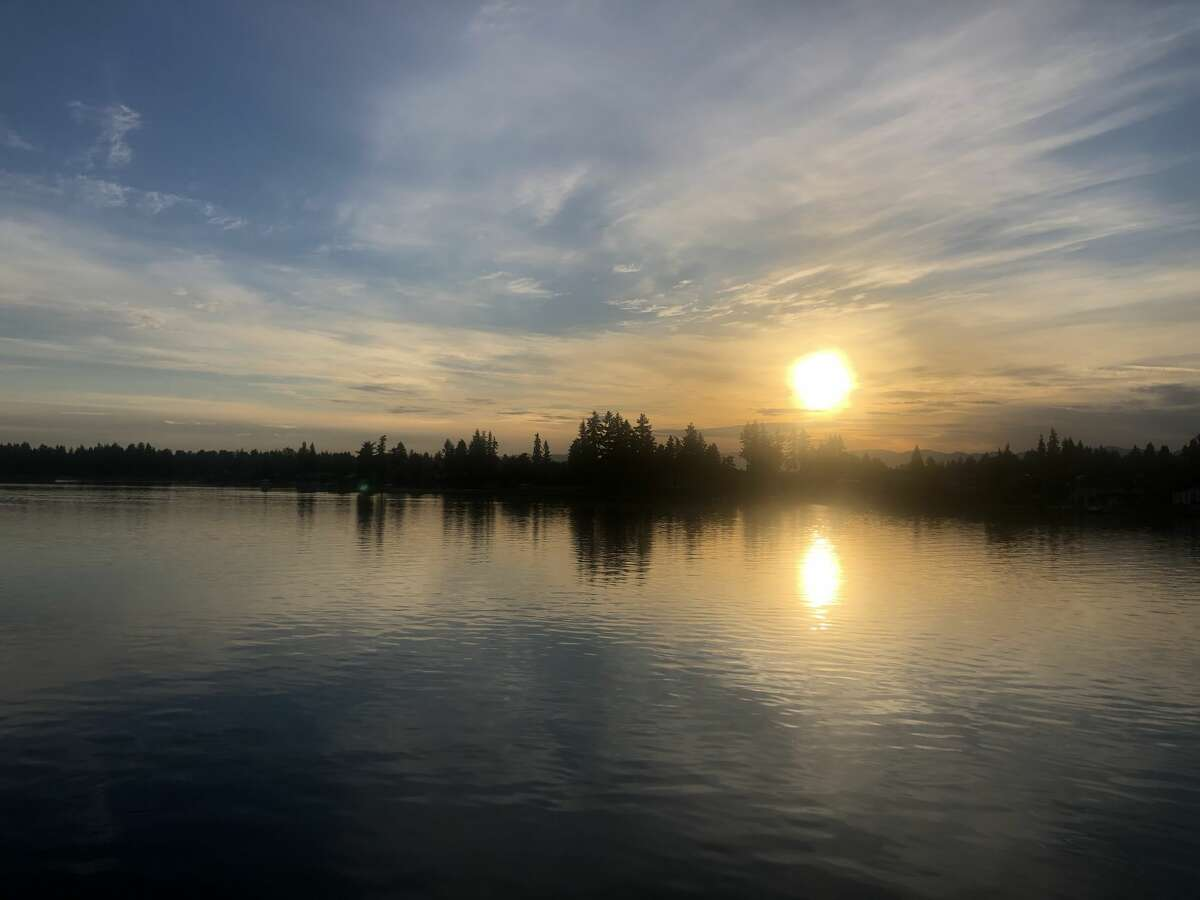 A Seattle Ballooning hot air balloon lowers over Lake Tapps briefly.